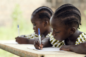 Fototapeta African Children at School Doing Homework. African ethnicity students writing their essay in an African school. They're holding blue pens to write down their homework whilst sitting in their desk.