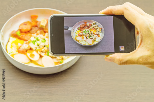 Foto  Hand of girl taking pictures on a mobile phone in Indochina pan-fried egg with t