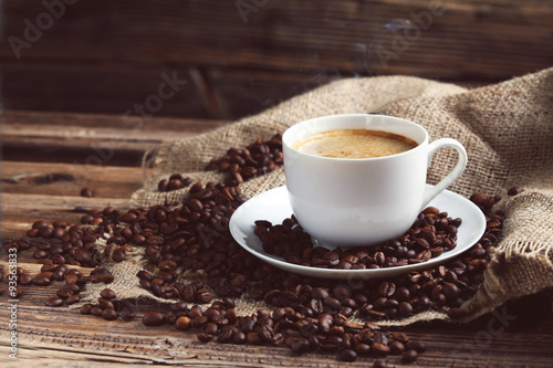 Deurstickers koffiebar Cup of coffee with coffee beans on a brown wooden background