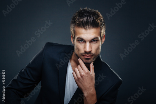 obraz dibond Portrait of handsome man in a studio on a dark background