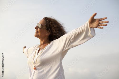 Valokuvatapetti Mujer con los brazos abiertos hacia el sol