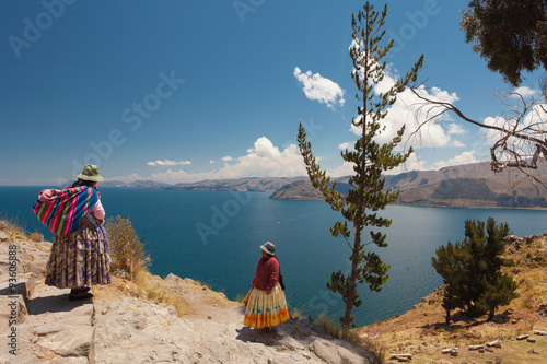 Photo Two Women In Traditional Bolivian Clothes Standing On The Rock Close To The Titicaca Lake
