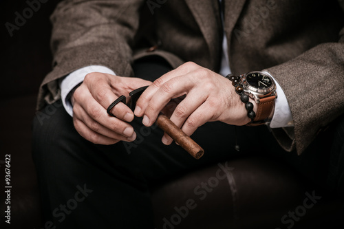 Obraz na płótnie elegant man wearing suit and white shirt cut Cuban cigar indoor shot, closeup, s