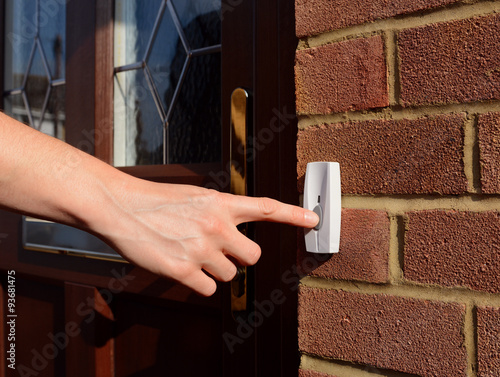 Fotografie, Obraz  Woman extends her hand to ring doorbell