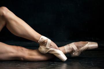 Fototapeta Close-up ballerina's legs in pointes on the black wooden floor