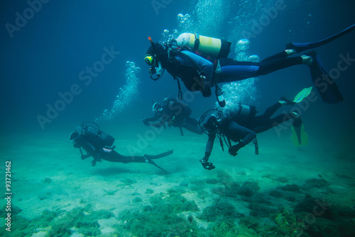 Foto op Canvas Duiken Four divers underwater