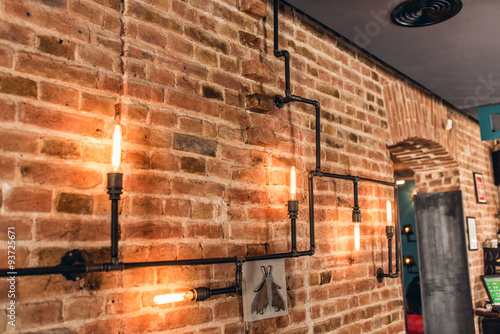 Fototapeta restaurant rustic walls, vintage interior design lamps, metal pipes and light bu