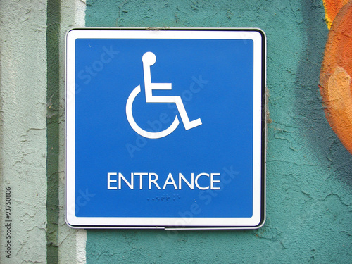 handicap entrance sign on painted stucco wall buy this stock photo