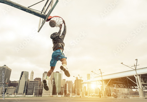 Foto  Basketball street player making a rear slam dunk
