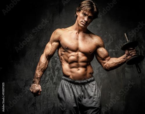 Fotografia  Shirtless bodybuilder holding dumbell.
