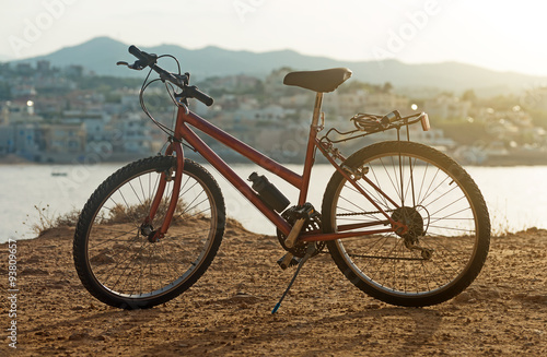 Fotobehang Fiets Red bicycle on the hill at sunset.