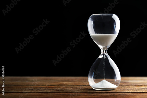 Fotografiet  Hourglass on wooden table on grey background