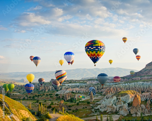 Poster Montgolfière / Dirigeable Colorful hot air balloons flying over Red valley at Cappadocia,
