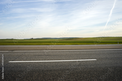 Fotografia highway and field against blue sky