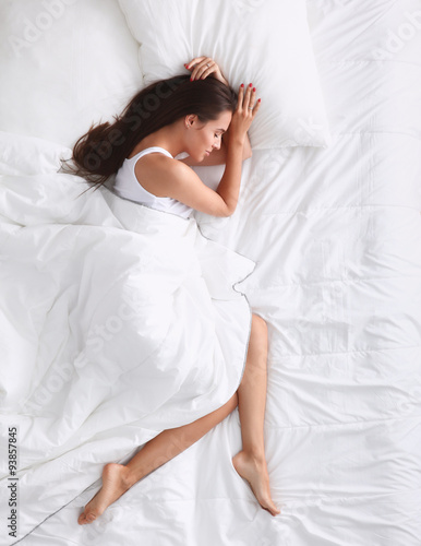 Photo  Young beautiful woman lying in bed