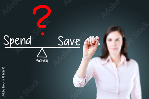 Fotografía  Young business woman writing spend and save compare on balance bar