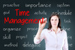 Young business woman writing time management concept. Blue background.