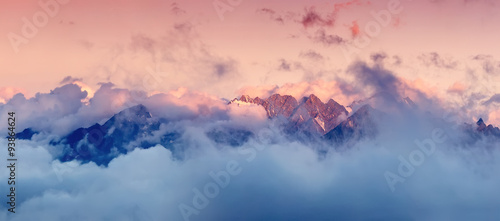 Aluminium Prints Mountains High mountain range in the clouds during sunrise. Beautiful panoramic landscape