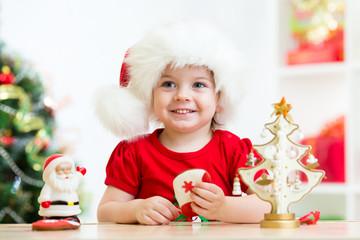 FototapetaLittle girl child wearing a festive red Santa hat with Christmas