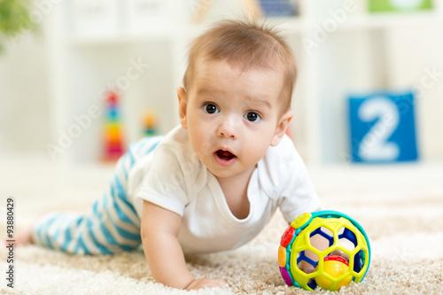 Joyful baby crawling on the floor in nursery room Canvas Print