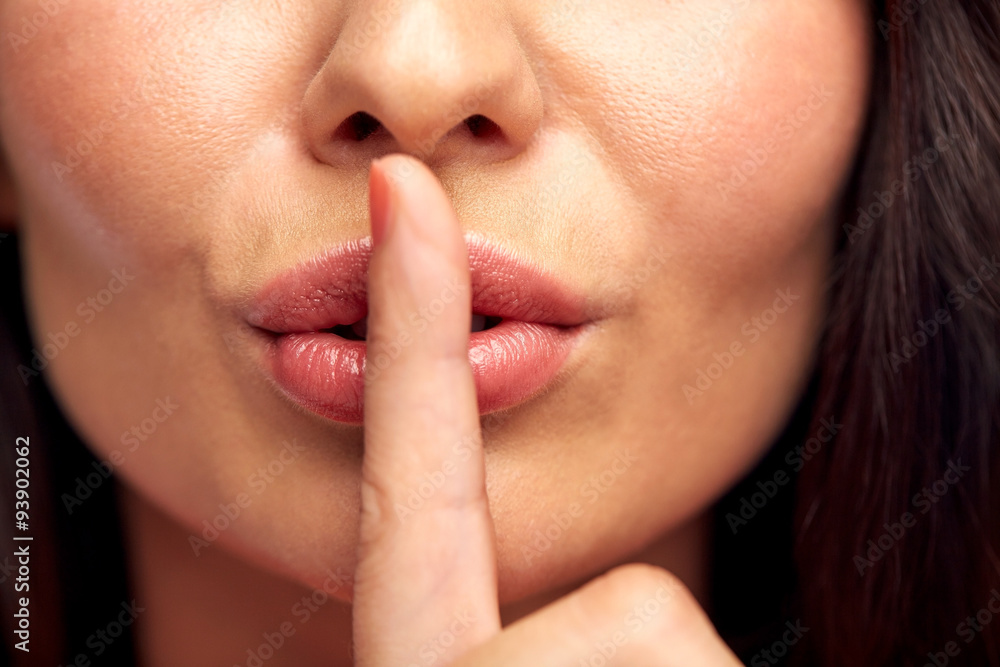 Fototapeta close up of young woman holding finger on lips
