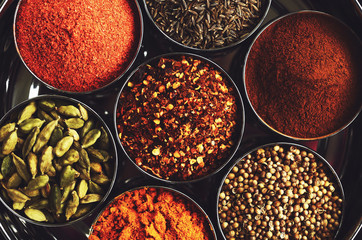 Rack with traditional indian spices for cooking - cardamom, turmeric, cumin, coriander seeds, cinnamon and chili