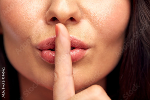 Photo  close up of young woman holding finger on lips