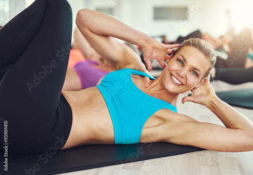 Fototapety, obrazy: Smiling woman doing abdominal exercises on mat in gym