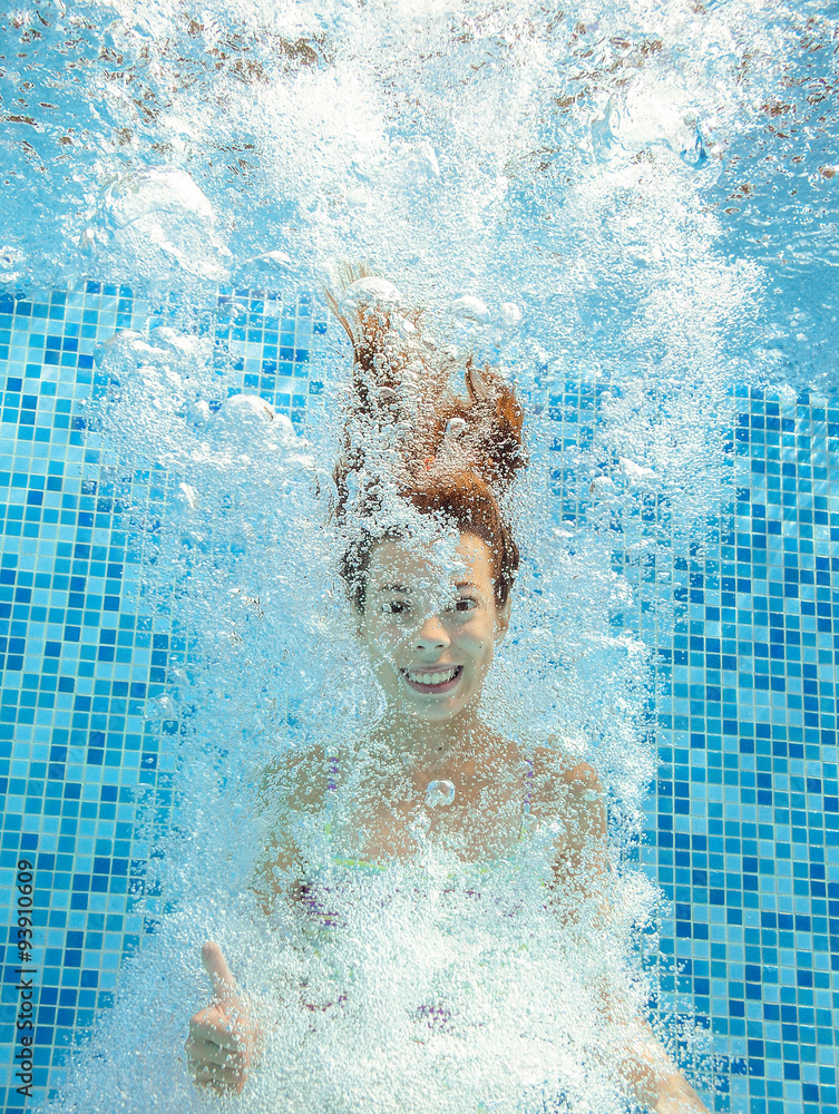 Photo  Girl jumps and swims in pool underwater, happy active child has fun in water