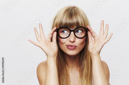Fotografiet  Beautiful woman adjusting spectacles in studio