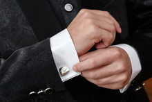 The Man Clasps A Cuff Link On A Shirt