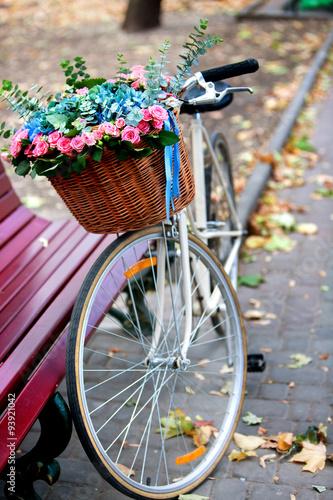 Fotobehang Fiets Bike with basket of flowers in Park.