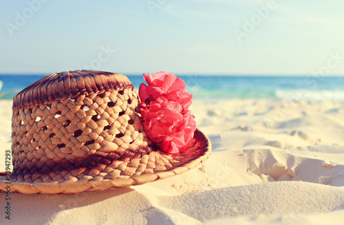 Handmade artisan caribbean straw hat and tropical pink flower on white sand, blue sea backdrop. Relaxing beach background. Warm vintage tonality.