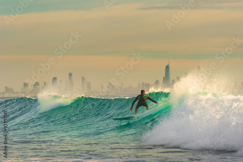 Fényképezés  Surfer Surfing a wave with Surfers Paradise in the Background