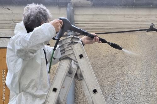 homme nettoyant façade avec eau à haute pression