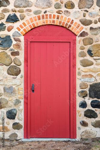 czerwone-lukowate-drzwi-w-kamiennej-scianie