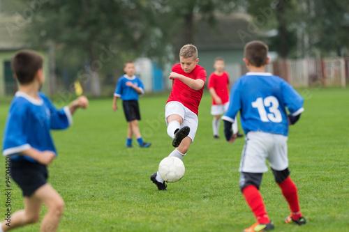 Fotografiet  boy kicking football