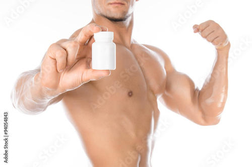 Fotografia  Bodybuilding and chemical additives: handsome strong bodybuilder holding a white