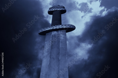 Medieval viking sword against a dramatic sky Poster