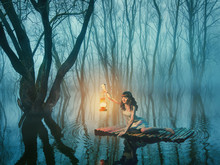 Fairy Tale Woman With Lantern Floating On The Lake In The Misty Forest In Rustic White Dress.