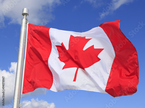 Spoed Foto op Canvas Canada Canadian flag waving on the wind withe blue sky and white clouds background