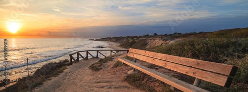 Bench along an outlook with a view at sunset of Crystal Cove Beach, Newport Beac Fotobehang