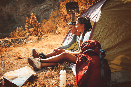 Tuinposter Kamperen Couple camping. Young couple sitting in tent and relaxing.