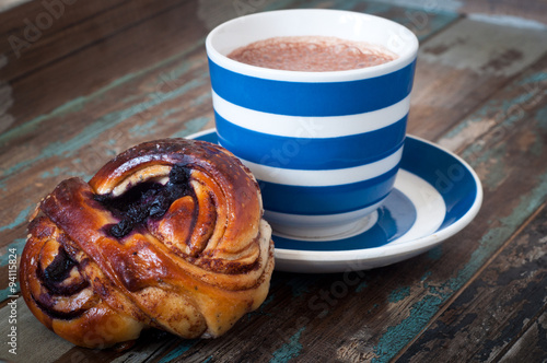 Fotografía  Swedish cinnamon berry bun served on a rustic wooden table with a cup of freshly brewed coffee in a blue and white striped cup and saucer