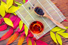 Infusion Of Hawthorn In A Glass Bowl, A Wooden Spoon With Dry Fruits And Bamboo Mat On The Table With Bright Yellow And Crimson Autumn Leaves