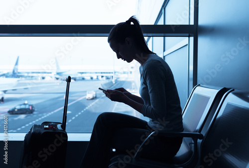Fotografie, Obraz  Woman using mobile smart phone at the airport