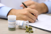 Doctor Writing On Prescription Blank And Bottle With Medical Cannabis On Table Close Up