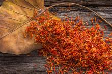 Dry Safflower With Leaf  On Grunge Wooden Background.