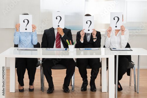 Fotografie, Obraz  Businesspeople Hiding Face With Question Mark Sign
