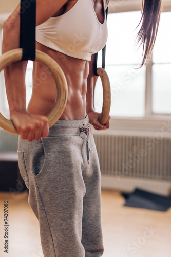 Muscular woman at gym doing dipping exercise Canvas Print